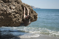 Summer climbing. Smiling young person climbing under the water in a sunny day Stock Photo