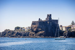 Summer close the Castle. The ancient castle of Aci Castello in Sicily at summer time In the foregound a sail boat anchored at the roadstead stock photos