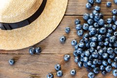 Summer close-up of blueberries and straw hat on vintage wooden background. Top view of ripe and juicy fresh picked bilberries. Pretty beautiful straw hat with Royalty Free Stock Photography