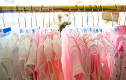 Summer clothes. A row of pink summer clothes hanging on hangers stock image