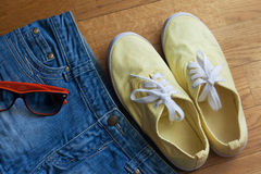 Summer clothing. Preparing to summer. Shorts, sunglasses and yellow sneakers royalty free stock photos