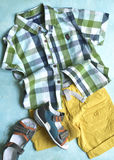 Summer clothing set for boy.Top view. Summer clothing set for boy on a light blue slate,stone or concrete background.Top view Stock Photos
