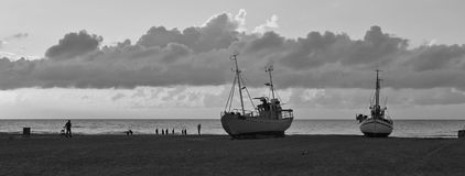 Summer clouds over the Jammerbugten, Denmark. Beach scene at Slettestrand. Fishing boats on the shore. Quiet evening at the Slettestrand, Denmark. Fishing boats stock images