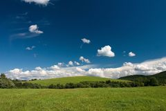 Summer cloudscape. Summer landscape with cumulus and green meadows stock photo