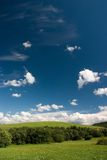 Summer cloudscape. Summer landscape with cumulus and green meadows royalty free stock photo