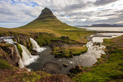 Summer cloudy day with Kirkjufell volcano on the coast of Snaefellsnes peninsula. Idyllic scene of Kirkjufellsfoss waterfall, Icel stock photography