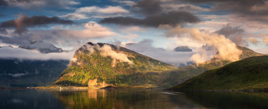Summer cloudy panorama of Lofoten Islands, Norway. Summer sunset panorama of Lofoten Islands, Norway, with mountains, fjord, and beautiful clouds illuminated by Royalty Free Stock Photos