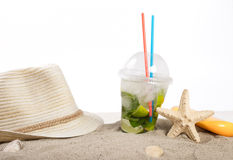 Summer cocktail with beach accessories in the sand close up Stock Photo