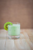 Summer cocktail of kiwi fruit and ice cream on a wooden background Stock Images
