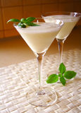 Summer coctail. Coconut milk coctail in martini glass with basil leaflets on top