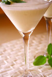 Summer coctail. Coconut milk coctail in martini glass with basil leaflets on top stock photo