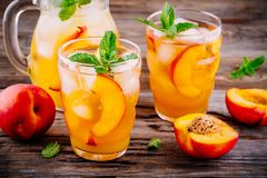 Summer cold drinks: homemade peach sangria with ice cubes, and mint in glasses Royalty Free Stock Photo