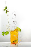 Summer cold Iced tea. With fresh mint and lemon in glass with splashes on light table, grey wall at background, copy space. Food in motion concept Stock Photography