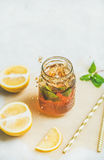 Summer cold Iced tea with lemon and herbs, copy space. Summer cold Iced tea with fresh bergamot, mint and lemon in glass jar with splashes on light table Royalty Free Stock Photos