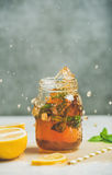 Summer cold Iced tea with lemon and herbs. Summer cold Iced tea with fresh bergamot, mint and lemon in glass jar with splashes on grey table, grey concrete wall Stock Images
