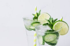 Summer cold transparent drink with ice cubes, slices lime, cucumber, straw and twigs mint on white wood board, closeup. royalty free stock images
