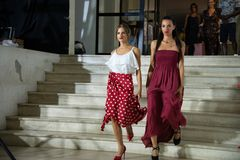 Two girls parade with dresses in white top with viscose flounce combined with white polka dot wallet skirt, red background and ele royalty free stock image