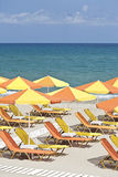 Summer colorful vacation. Colorful yellow-orange sun chairs and umbrellas arranged in rows. Sea represents as a contrast background. Vertical image Stock Photography