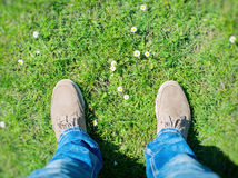 Summer is coming!. Male boots on the grass with first flowers. Top view Stock Photo