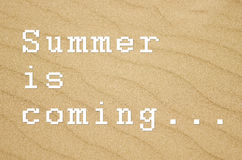 Summer is coming... written on sandy background. Stock Images
