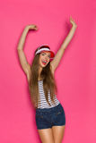 Summer Is Coming. Young beautiful woman in jeans shorts, striped shirt and red sun visor posing with arms raised and shouting. Three quarter length studio shot Royalty Free Stock Photos
