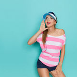 Summer Is Comming. Girl in pink striped shirt, jeans shorts and blue sun visor, holding hand on chin, looking away and announces message. Three quarter length Stock Images