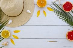 Summer composition. Fruits, hat, tropical palm leaves, seastones on pastel yellow white wooden background. Summer. Concept. Flat lay, top view, copy space Royalty Free Stock Images