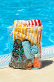 Summer concept. Handbag at poolside in hot summer day. It contains sunglasses, towel, bikini and suntan Stock Images
