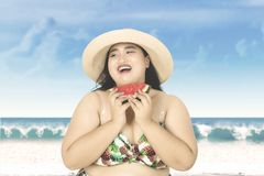 Woman eats watermelon at coast. Summer concept. Cheerful overweight woman wearing bikini on the beach while eating a fresh watermelon Royalty Free Stock Photos