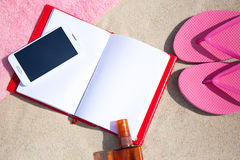 Summer concept - flip flops, towel, phone, book and suntan lotio Royalty Free Stock Photos