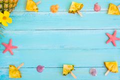 Frame made of pineapple popsicle sticks, starfish and shells on wood plank blue color. Summer concept. Frame made of pineapple popsicle sticks, starfish and royalty free stock images