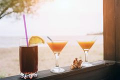 Summer concept: fresh exotic cocktails on wooden edge. Shell lying between glasses. Cola with straw and lemon. Island. Life. Paradise royalty free stock photos