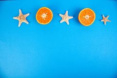 Summer concept. Orange fruit and starfish. On blue paper background. Flat lay. Copy space Royalty Free Stock Photos