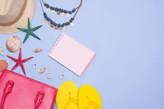 Summer concept. Pink handbag with accessories on light blue back Stock Images