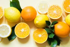 Summer concept. Set of tropical fruits, lemon, orange and green leaves on yellow. Close up. Top view. royalty free stock photo