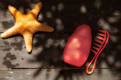 Summer Concept. Starfish, Suntan Lotion and Comb Royalty Free Stock Images