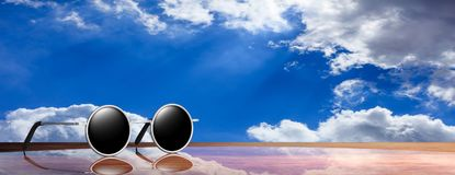 Sunglasses silver round frame with black lens, on wooden surface and a sky background, banner, 3d illustration. Royalty Free Stock Image