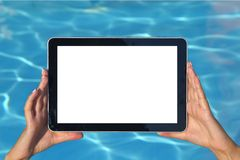 Summer concept. Woman holding tablet computer. Woman hand holding tablet computer in the pool Royalty Free Stock Photo