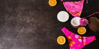 Summer conceptual photography. Pink swimsuit, coconut, orange, cocktail umbrellas on a dark marble background. Summer concept royalty free stock photography