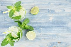 Summer cool lemonade in two wet glasses with mint, lime, ice, straw on soft shabby blue wood board, copy space, top view. Summer cool lemonade in two wet Royalty Free Stock Images