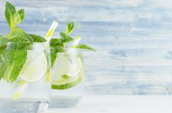 Summer cool lemonade in two wet glasses with mint, lime, ice, straw on vintage blue wood board, copy space, closeup. Stock Images