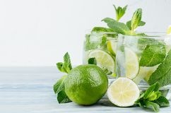 Summer cool lemonade in two wet glasses with mint, lime, ice, straw on vintage white plaster background, copy space, closeup. Summer cool lemonade in two wet stock photography