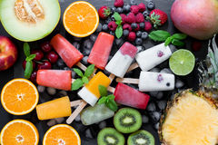 Summer coolness of ice cream and sorbet cones. In the center on ice cubes variety of sorbet and ice cream cones near ingredients fruits and berries on black Royalty Free Stock Images