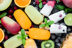 Summer coolness of ice cream and sorbet cones. In the center on ice cubes variety of sorbet and ice cream cones near ingredients fruits and berries on black Royalty Free Stock Photo