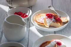 Summer cottage cheese pancakes on white plates on a wooden table with coffee, milk, sour cream and jam, closeup Stock Photography