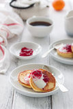 Summer cottage cheese pancakes on white plates on a wooden table with coffee, milk, sour cream and jam, closeup Royalty Free Stock Photography