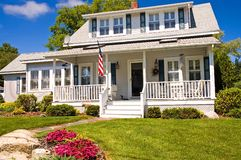 Summer cottage with porch. A view of a comfortable two-story Cape style summer cottage with large porch at the seacoast in Maine Stock Photography