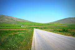Summer country road. Country road in green hill scenery against nice blue sky Stock Images