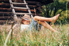 Summer in the countryside - little boy lies near the hayloft Stock Image
