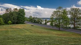 summer countryside. View from a sloping hill on a country asphalt road along the coast of a large lake Royalty Free Stock Images